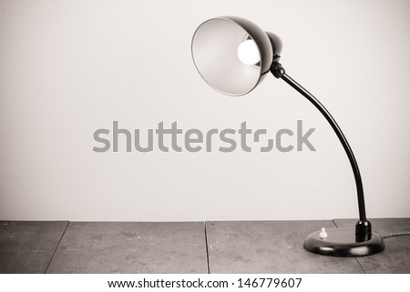 Black retro desk lamp with lighting bulb - stock photo