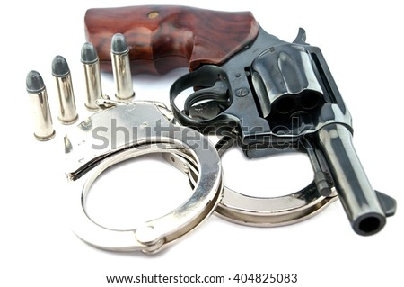 black revolver handgun and police handcuff with bullets isolated on isolate background. (gun target firearms shoot sights violence) - stock photo