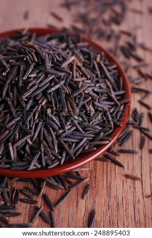 Black rice on plate on wooden background - stock photo