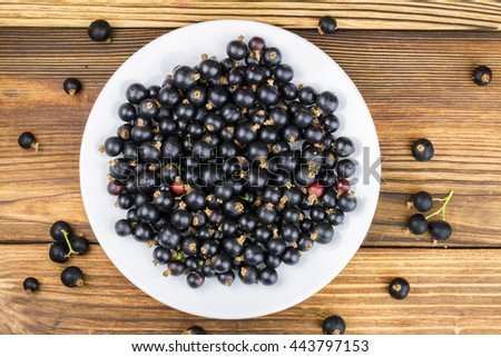 Black ripe currant in white plate on wooden background, top view, flate image - stock photo