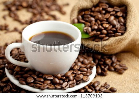 black roasted arabica coffee beans and cup full of coffee - stock photo