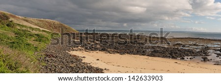 Black rocky beach on Philip Island beach on cloudy day panorama with bright light spots on green grass and sand with hills and breaking waves in background in Victoria, Australia - stock photo