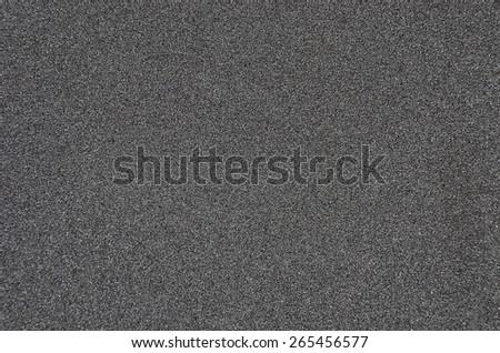 Black rough textured sandpaper background, close up - stock photo
