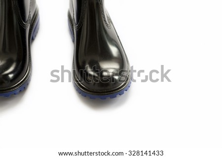 Black rubber boots blue outsole on white background - stock photo