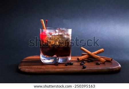 Black Russian Cocktail  made with vodka, coffee liqueur and cream. Coffee beans garnish and cinnamon stick and red cherry on  wooden cutting board - stock photo