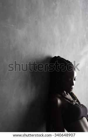 black sad woman in underwear leaning against the wall . The concept of hopelessness , loneliness , sadness , loss . A lot of free space on a gray background. - stock photo