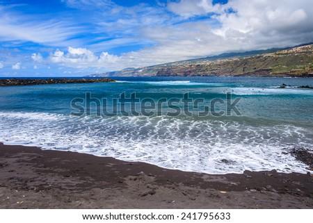 Black sand volcanic beach in Puerto de la Cruz town, Tenerife, Canary Islands, Spain - stock photo