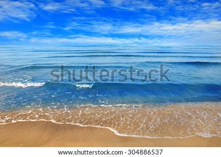 Black sea beach blue sky sand sun daylight - stock photo