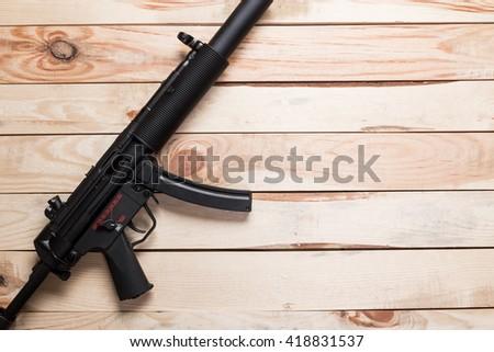 black semi-automatic gun on old wood background. - stock photo