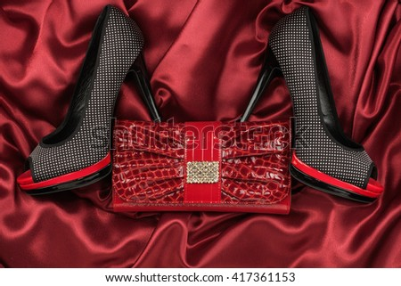 Black shoes and purse lying on the red satin, top view - stock photo