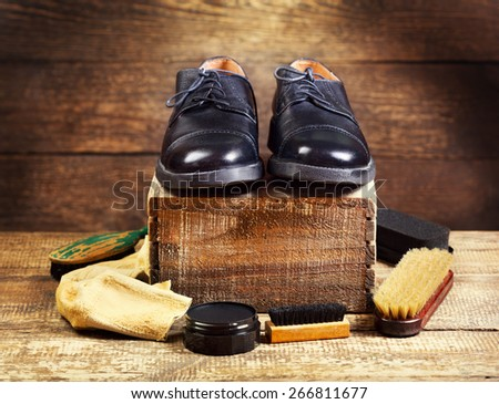 black  shoes with care accessories on a wooden background - stock photo