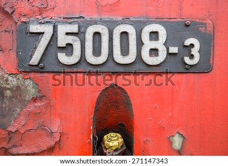 Black sign of old locomotive on a red background. - stock photo