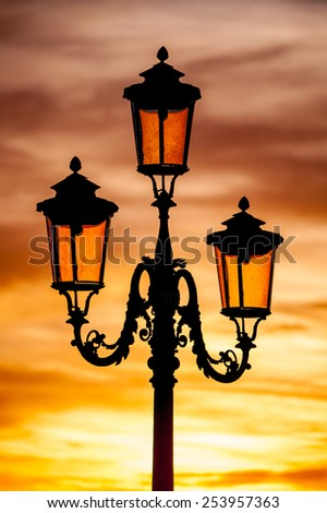 Black silhouette of fancy wrought iron venetian lantern lamp glows orange light at the sun illuminates on beautiful orange sunset sky background - stock photo