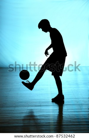 Black silhouette of footballer on blue background - stock photo
