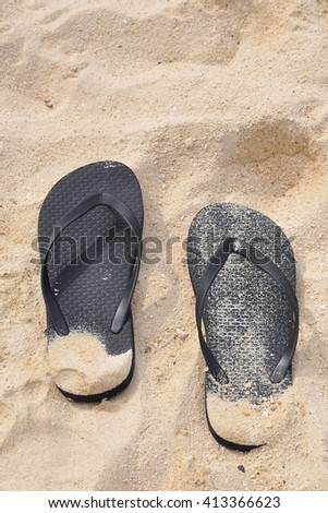 Black slippers on the sand - stock photo