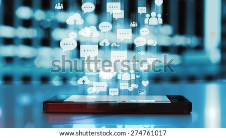 Black smart phone emitting blue holographic images of social media related icons.  - stock photo