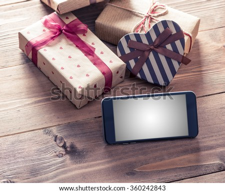 Black smart phone near gift boxes. Clipping path included. - stock photo