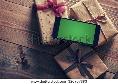 Black smart phone on a heap of gift boxes. Clipping path included. - stock photo