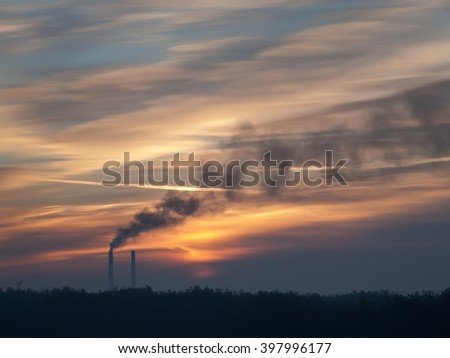 Black smoke on background beautiful sky during sunset. Smoke is formed from thermal power plants. Smoke dissipate across the sky and turns to smog. Theme of global warming and environmental pollution. - stock photo