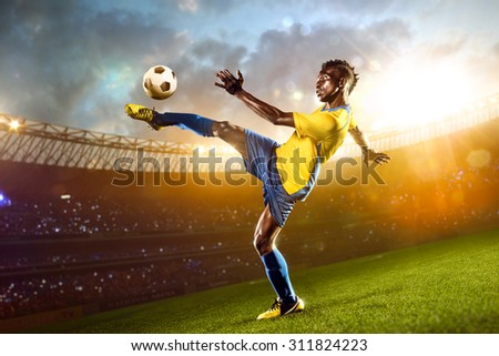 Black soccer player in action. Stadium field - stock photo