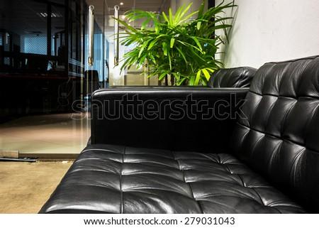 Black sofa in office - stock photo