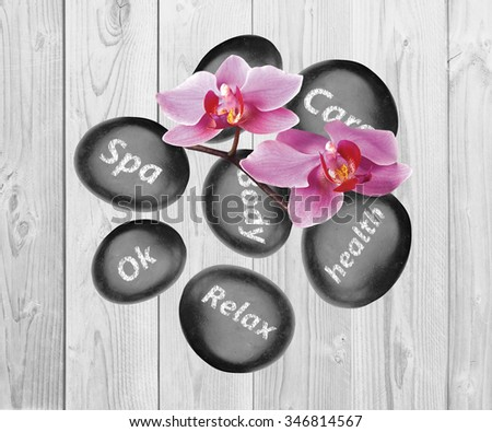 Black spa stones and orchid flowers on wooden background - stock photo