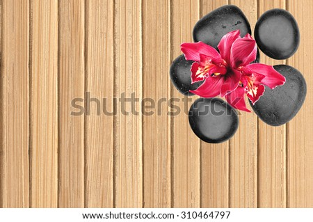 Black spa stones and pink orchid flower on wooden background - stock photo