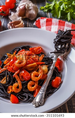 Black spaghetti with prawns and tomato garlic sauce. - stock photo
