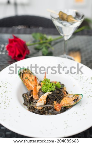 Black spaghetti with seafood and cocktail - stock photo