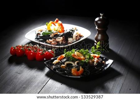 Black spaghetti with seafood on black table - stock photo