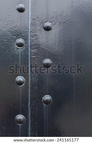Black steel metal with water erosion and rivet screws - stock photo