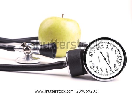 Black stethoscope and sphygmamanometer with green apple in the background isolated on white - stock photo