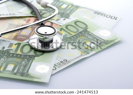 Black stethoscope close-up on top of euro banknotes side view - stock photo