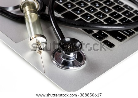 Black Stethoscope Closeup and Glass Syringe On Silver Laptop  With White Background - stock photo