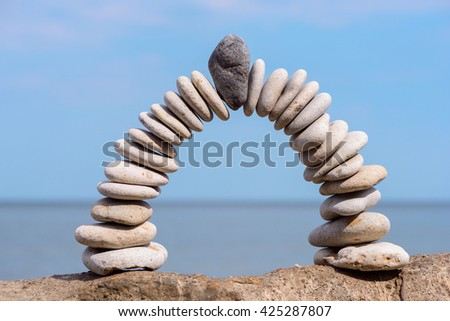 Black stone in the centre of arch of white pebbles - stock photo