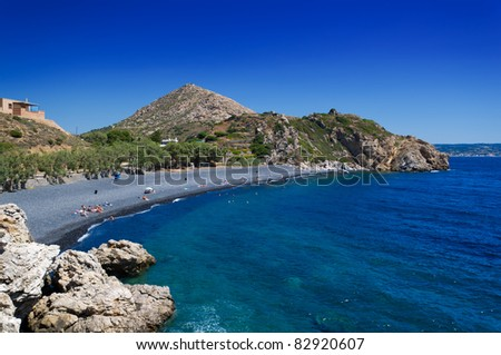 Black stones beach in chios island - stock photo