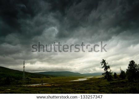 Black stormy sky in the rain in the mountains. Altai. Russia - stock photo