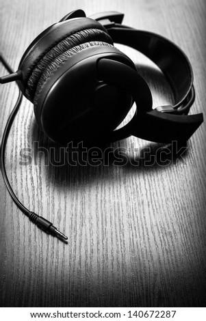 black studio headphones lying on a wooden background - stock photo