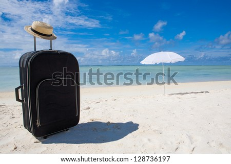 black suitcase sun hat and white sunshade at the beach - stock photo