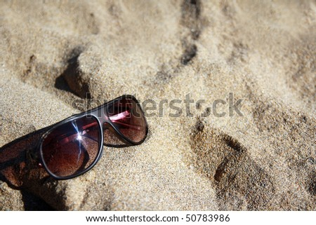 Black sunglasses on sand - stock photo