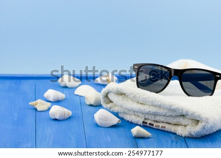 Black sunglasses with shells and white towel on wooden vintage blue background - stock photo