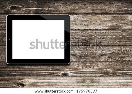 Black tablet computer with isolated screen on an old wooden desk - stock photo