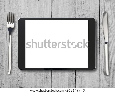 black tablet pc on wooden table with fork and knife - stock photo