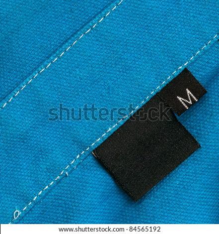 Black tag on blue a cotton textile - stock photo