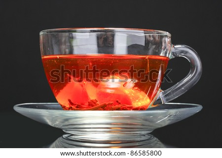black tea and fruit in cup on black  background - stock photo