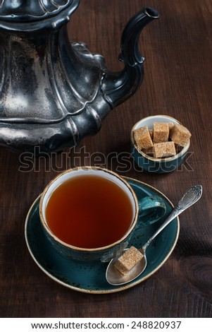 Black tea in the blue vintage cup and antique silver coffee pot on a old dark wooden boards - stock photo