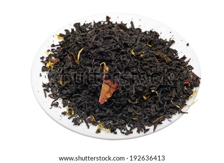 Black tea with flower petals and spices on a white background. - stock photo