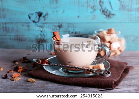 Black tea with milk and lump sugar and spices  in glassware on color wooden planks background - stock photo