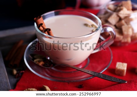 Black tea with milk and lump sugar on wooden tray with napkin and color wooden planks background - stock photo