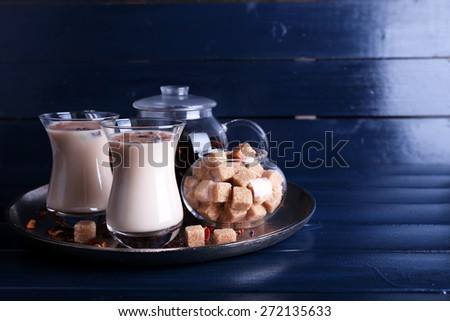 Black tea with milk in glasses and teapot with lump sugar on metal tray and color wooden planks background - stock photo